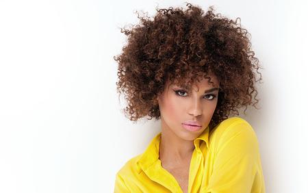 아프리카와 매력적인 메이크업으로 아름 다운 젊은 아프리카 계 미국인 여자의 초상화. 스튜디오 촬영. 노란색 유행 드레스입니다.
