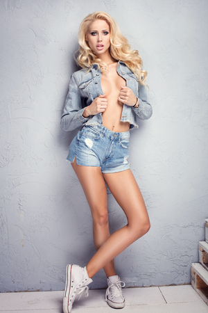 Photo of blonde young sexy woman in jeans short and jacket. Studio shot. Glamour makeup. Ideal body. Standard-Bild