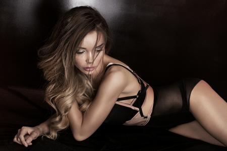 Sinnlich schöne Frau mit schwarzen Dessous, im Bett liegen. Sexy Körper. Glamour Make-up.