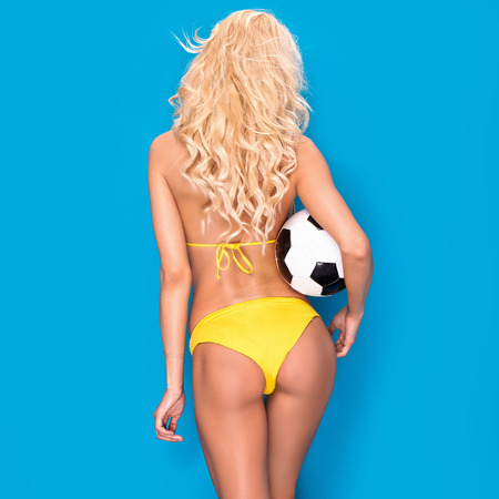 Sexy blonde woman as a soccer player. Fit body shape.