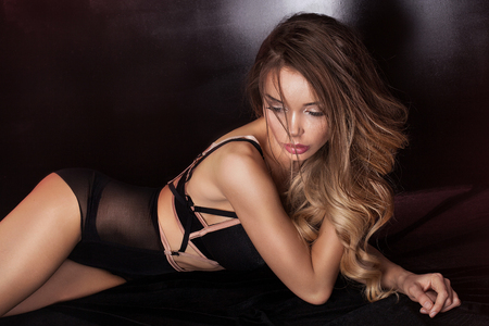 Sensual beautiful woman wearing black lingerie, lying in bed. Sexy body. Glamour makeup. Stock Photo