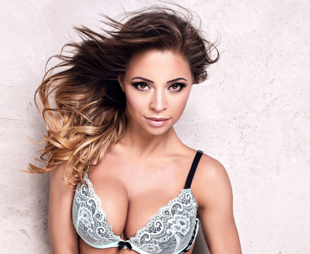 Sexy attractive brunette woman posing in fashionable lingerie, studio shot. Perfect slim body.