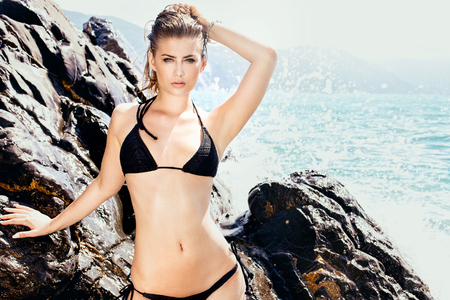 beach breast: Beautiful young woman posing on the rocky beach, summer photo. Girl wearing black bikini. Stock Photo