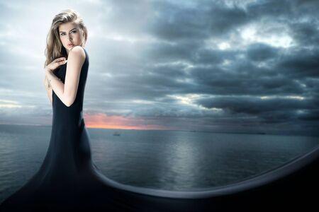 maxi dress: Elegant beautiful young woman posing in black dress. Sea on background.