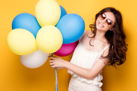 Young pretty teenage girl posing over yellow background, holding colorful balloons, wearing fashionable sunglasses. Summer style. Studio shot.