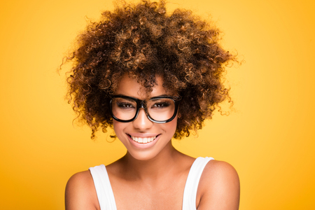 Young beautiful african american girl with an afro hairstyle. Laughing girl wearing eyeglasses. Portrait. Yellow background. Girl looking at camera. Фото со стока