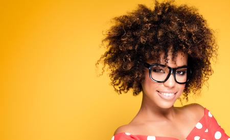 Portrait de sourire belle afro-américaine jeune femme. Fille avec des lunettes portant afro. Fond jaune. Studio shot.