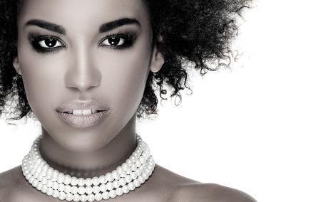 아프리카 젊은 우아한 아프리카 계 미국인 여자의 아름다움 사진. 소녀는 진주를 입고. 카메라를 찾고. 매력적인 메이크업. 스튜디오 촬영.