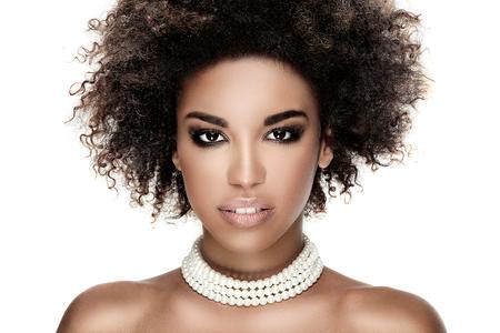 Beauty foto van jonge elegante Afrikaanse Amerikaanse vrouw met afro. Meisje dragen van parels. Kijkend naar de camera. Glamour make-up. Studio-opname.