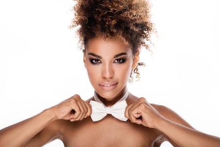 Schönheit Porträt African American Frau mit Afro-Frisur. Mädchen tragen weiße Fliege. Betrachtet man die Kamera. Studio gedreht. Weißer Hintergrund. Standard-Bild - 61284328