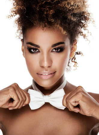 Beauty portrait of african american woman with afro hairstyle. Girl wearing white bow tie. Looking at camera. Studio shot. White background.