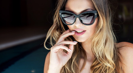 Portrait of sexy attractive blonde woman posing. Girl wearing fashionable sunglasses.