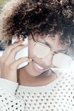 telephoning: Portrait of young african american girl with afro and fashionable sunglasses. Girl talking by mobile phone, smiling. Sunny day. Outdoor photo.