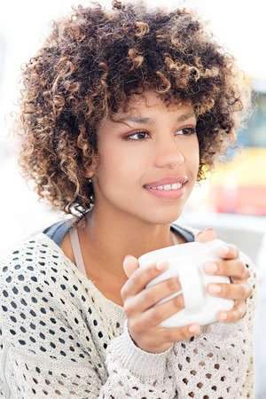 Young beautiful african american student sitting at cafe. Girl with afro holding white mug, drinking hot coffee.