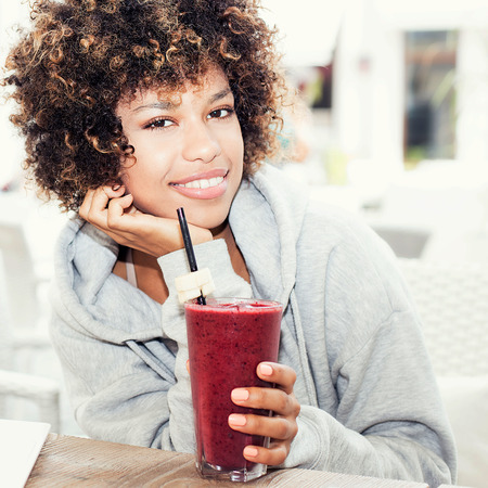 fruity: Young beautiful african american student sitting at cafe. Girl with afro drinking fruity coctail.
