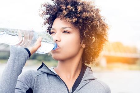 Close up retrato de agua potable mujer joven atractiva de botella. Persona que practica jogging.