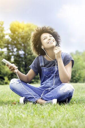 Young african american teenager girl using smartphone and headphones, listen to music, park, outdoor.