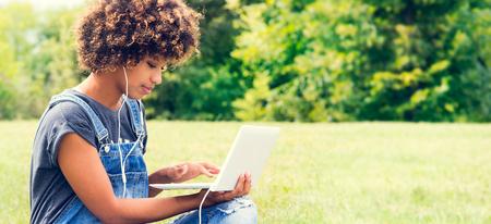 Junge weibliche African American Frau, die einen sonnigen Tag im Park genießen, arbeiten am Computer. Schüler.