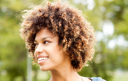 Portrait of young beautiful african american girl with afro hairstyle. Girl smiling. Outdoor shot. Stock Photo