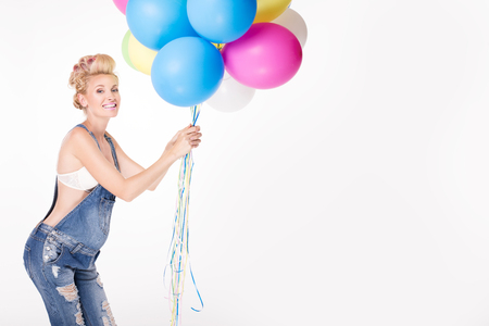 Happy pregnant woman posing in studio with colorful balloons. Stock Photo