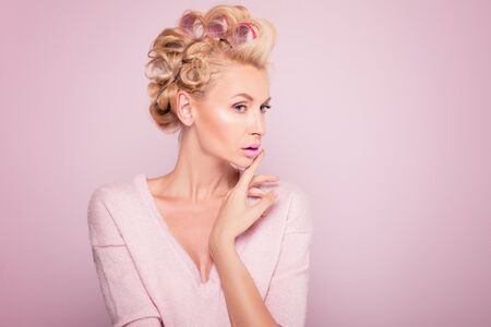 hot rollers: Beauty potrait of young blonde woman with glamour makeup and hot rollers. Pink background. Beauty concept.