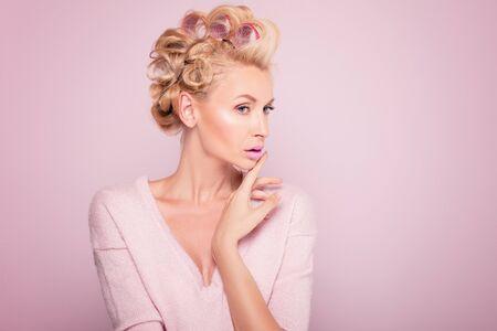 Piękna potrait młoda blondynki kobieta z splendoru makeup i gorący rolownikami. Różowe tło. Pojęcie piękna.