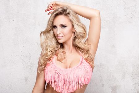 Portrait of beautiful blonde girl with long curly hair. Girl posing in pink fashionable bikini, looking at camera. Studio shot.