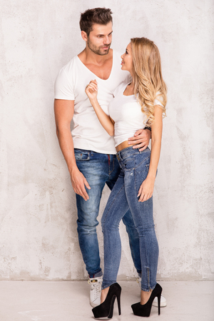 Sexy beautiful couple posing, wearing fashionable jeans. Studio shot. Attractive blonde woman and handsome man. Stock Photo
