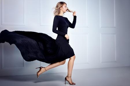 Bella donna elegante bionda posa in abito maxi nero, guardando a porte chiuse. tiro al coperto.