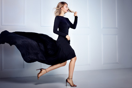 Mooie elegante blonde vrouw die zich in zwarte maxi jurk, camera kijken. Binnen schot.