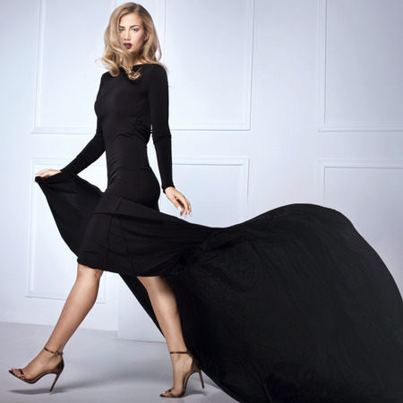 maxi: Beautiful elegant blonde woman posing in black maxi dress, looking at camera. Indoor shot.