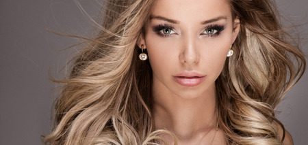 Closeup beauty portrait of beautiful woman with glamour makeup and long curly hair. Standard-Bild