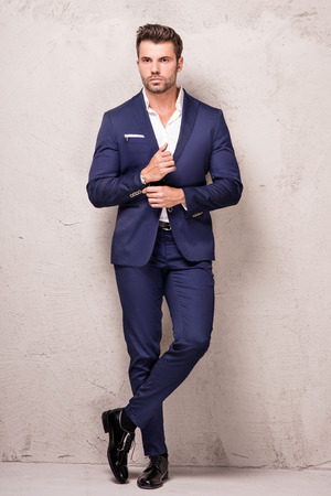 Elegant young handsome man posing in fashionable suit, looking at camera. Studio shot.