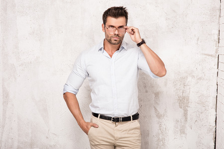 casual men: Handsome young man posing in fashionable shirt and eyeglasses. Studio shot.