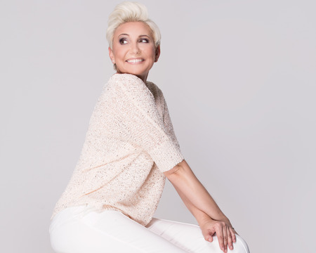 Fashionable beautiful adult woman posing in studio. Lady with blonde short haircut.