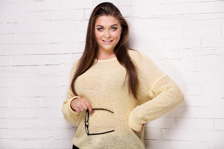 Portrait of beautiful brunette plus size model. Girl with long hair and glamour makeup.