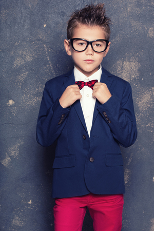 Elegant little boy wearing suit and eyeglasses. Studio shot. Fashionable look. Small businessman.
