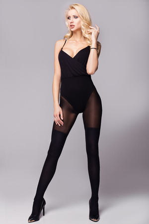 Sexy blonde woman with long legs posing in studio. Full body. Imagens