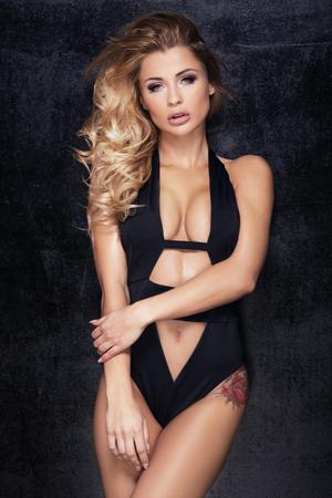 Junge blonde Frau, die im schwarzen modischen Badeanzug aufwirft. Mädchen mit idealem Körper. Studioaufnahme.