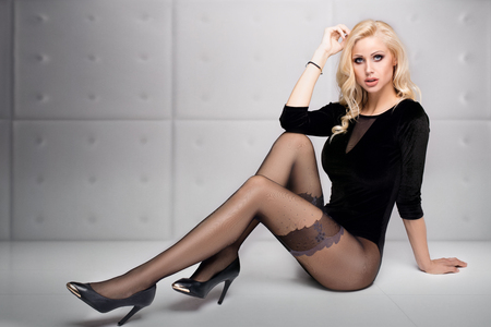 Beautiful blonde girl with long slim legs wearing tights , posing in studio. Full body. 写真素材