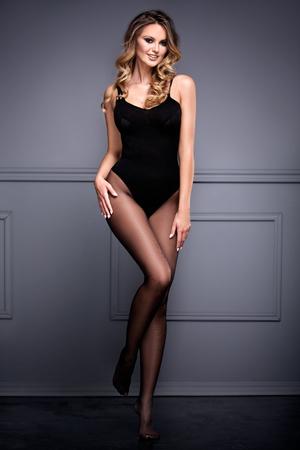 Beautiful blonde girl with long slim legs wearing tights , posing in studio. Full body. Imagens