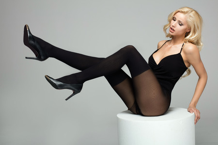 Beautiful blonde girl with long slim legs wearing tights , posing in studio. Full body. Фото со стока