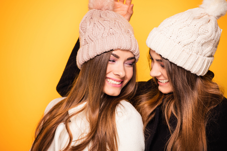 Happy young twins sisters posing, wearing fashionable caps. Yellow background.