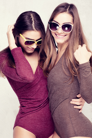 Twins sisters having fun together, wearing fashionable sunglasses, laughing. Studio shot.