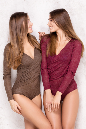 Beautiful young sisters twins posing together in studio, looking at camera. Two fashion models having fun, smiling.