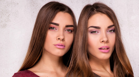 Beautiful young sisters twins posing together in studio, looking at camera. Two fashion models.