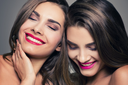 Fashion studio photo of two beautiful young ladys . Beauty portrait of twins sisters. Perfect face makeup. Smiling happy girls. Imagens