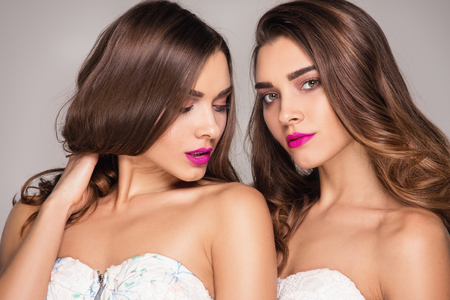 Fashion studio photo of two beautiful young ladys . Beauty portrait of twins sisters. Perfect face makeup.