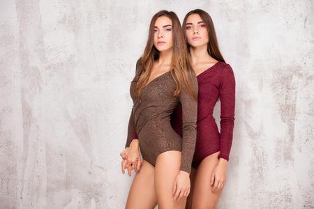 Schöne junge Schwestern Zwillinge posieren zusammen im Studio, Blick in die Kamera. Zwei Modemodelle.