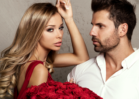 elegance fashion girls look sensuality young: Beautiful couple on date. Sexy blonde woman posing with handsome man, holding red roses.
